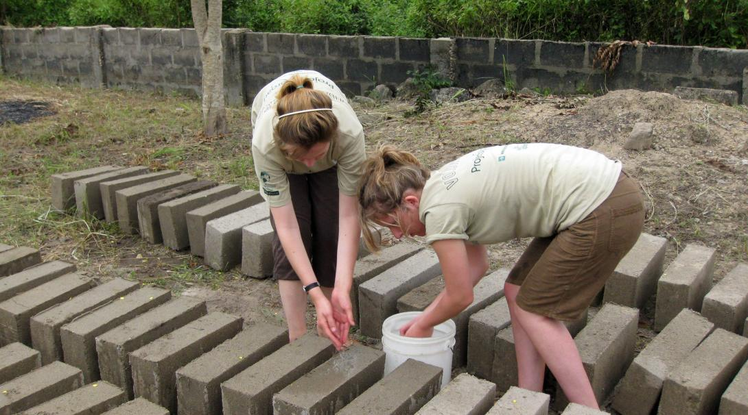 Voluntarias de construcción en Ghana preparando materiales.